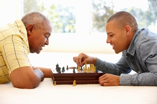 Senior man playing chess with son